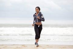 Mujer negra joven deportiva del cuerpo completo que corre en la playa por el agua fotos de archivo libres de regalías