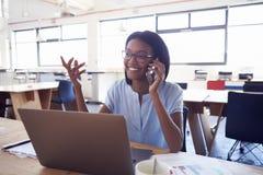 Mujer negra joven en el teléfono en el trabajo en un ½ del ¿del officeï fotos de archivo libres de regalías