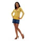 Mujer negra joven en falda de los pantalones vaqueros y tapa amarilla imagenes de archivo