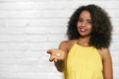 Mujer negra joven en la pared de ladrillo que toma píldoras de la vitamina Foto de archivo libre de regalías
