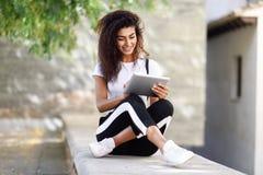 Mujer negra joven en ropa de deportes usando la tableta digital al aire libre imagen de archivo libre de regalías