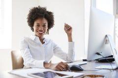 Mujer negra joven en una oficina que sonríe a la cámara, cierre para arriba imagen de archivo