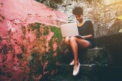 Mujer negra joven exquisita con netbook en paso pedregoso Imágenes de archivo libres de regalías