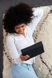 Mujer negra joven feliz que miente en una alfombra en casa y que usa la tableta digital para mirar el vídeo en línea Imagenes de archivo