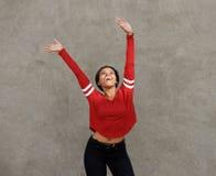 Mujer negra joven feliz que ríe con los brazos aumentados fotos de archivo