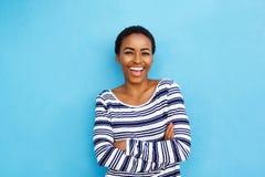 Mujer negra joven feliz que ríe contra la pared azul Imagen de archivo libre de regalías