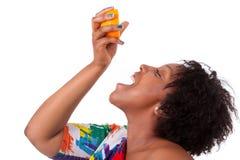 Mujer negra joven gorda que bebe el zumo de naranja - peo africano Foto de archivo