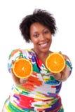 Mujer negra joven gorda que lleva a cabo las rebanadas anaranjadas - el PE africano Imagenes de archivo