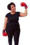 Mujer negra joven gorda que sostiene los guantes de boxeo - peo africano Fotos de archivo libres de regalías