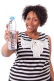 Mujer negra joven gorda que sostiene una botella de agua - p africano Foto de archivo libre de regalías