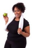 Mujer negra joven gorda que sostiene una manzana - gente africana Imagen de archivo libre de regalías