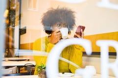 Mujer negra joven hermosa que mira el café de consumición del smartphone el café fotos de archivo