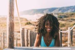 Mujer negra joven hermosa que se acuesta en un puente de madera del pie Imagenes de archivo