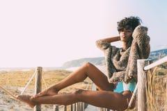 Mujer negra joven hermosa que se sienta en un puente de madera del pie en Fotografía de archivo