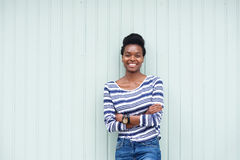 Mujer negra joven hermosa que sonríe con los brazos cruzados imagen de archivo libre de regalías