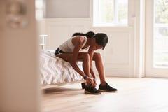 Mujer negra joven lista para ejercitar atando su zapato de los deportes Imagen de archivo libre de regalías