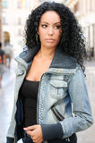 Mujer negra joven, peinado afro, en fondo urbano Imagen de archivo