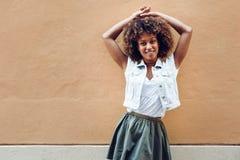 Mujer negra joven, peinado afro, sonriendo en fondo urbano fotografía de archivo