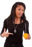 Mujer negra joven que bebe el zumo de naranja Fotografía de archivo libre de regalías