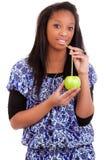 Mujer negra joven que bebe el zumo de naranja Foto de archivo libre de regalías