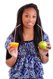 Mujer negra joven que bebe el zumo de naranja Fotos de archivo libres de regalías