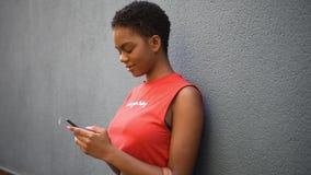 Mujer negra joven que manda un SMS con su teléfono elegante en fondo urbano metrajes