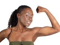 Mujer negra joven que muestra el bicep doblado fuerte Imágenes de archivo libres de regalías