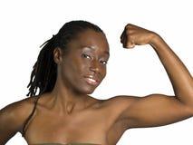 Mujer negra joven que muestra su músculo del bicep Foto de archivo