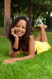 Mujer negra joven que se acuesta en la hierba Foto de archivo