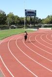 Mujer negra joven que se ejecuta en posibilidad muy remota de la pista Fotografía de archivo