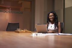Mujer negra joven que trabaja tarde en la oficina que sonríe a la cámara imagen de archivo
