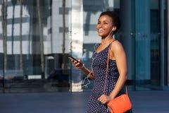 Mujer negra joven sonriente que camina con los auriculares y el teléfono móvil imagenes de archivo