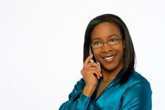 Mujer negra joven sonriente que habla en el teléfono móvil. Fotografía de archivo