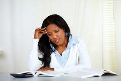 Mujer negra joven tensionada que lee un libro imagen de archivo libre de regalías