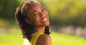 Mujer negra linda que sonríe en un parque Fotografía de archivo libre de regalías