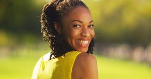 Mujer negra linda que sonríe en un parque Fotos de archivo libres de regalías