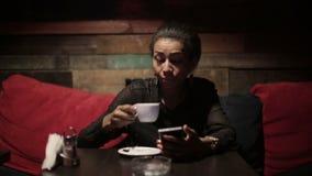 Mujer negra que bebe smartphones calientes del café y del uso metrajes