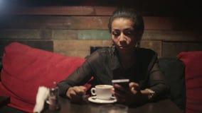 Mujer negra que bebe smartphones calientes del café y del uso