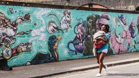Mujer negra que camina deteniendo a su hijo, delante encendido de una pared adornada en pintada Fotografía de archivo libre de regalías