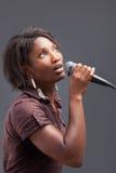 Mujer negra que canta en el micrófono Foto de archivo