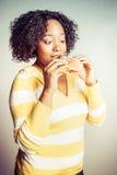 Mujer negra que come el bocadillo imagen de archivo libre de regalías