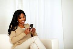 Mujer negra que envía un mensaje por el teléfono celular Fotografía de archivo