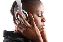 Mujer negra que escucha la música en los auriculares Imagenes de archivo