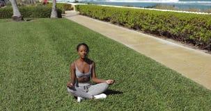 Mujer negra que hace yoga en césped almacen de video