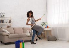 Mujer negra que juega Air Guitar con la fregona imágenes de archivo libres de regalías