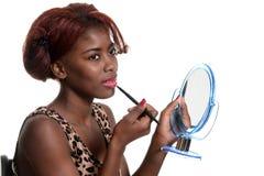 Mujer negra que pone en lustre rosado del labio Imagen de archivo libre de regalías