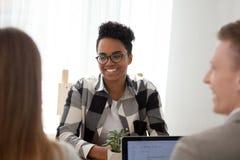 Mujer negra que se sienta así como colegas en oficina foto de archivo libre de regalías