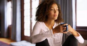 Mujer negra que se sienta solamente en casa con una taza de café Fotografía de archivo