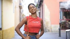 Mujer negra que sonríe en la cámara que parece confiada en calle urbana metrajes