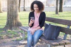 Mujer negra que usa el app en el teléfono móvil Fotografía de archivo